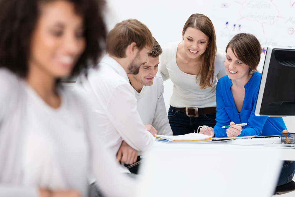 Diverse multiethnic group of young businesspeople in a meeting sitting at a table in the office discussing their business strategy and sharing information