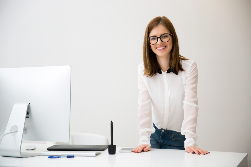 Portirrait of a beautiful smiling businesswoman standing near her workplace