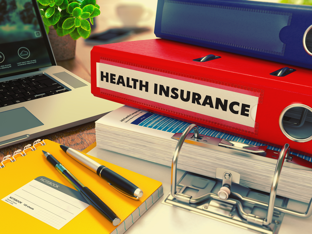 Red Office Folder with Inscription Health Insurance on Office Desktop with Office Supplies and Modern Laptop. Business Concept on Blurred Background. Toned Image.