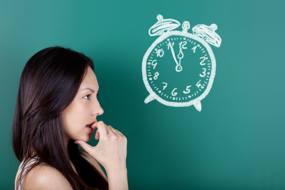 female student looking at a drawn clock showing five to twelve
