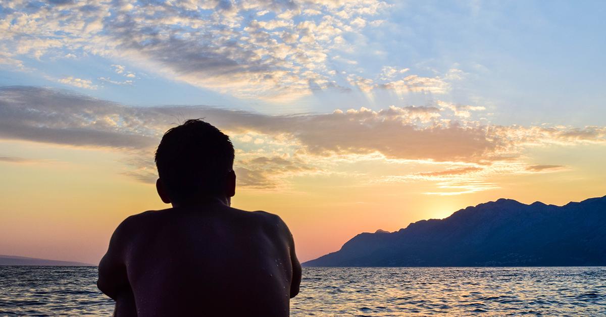 male-sitting-sunrise-beach-1200x628